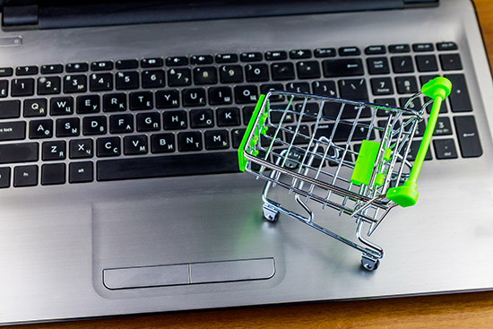 Online shopping concept. Small shopping cart on laptop keyboard